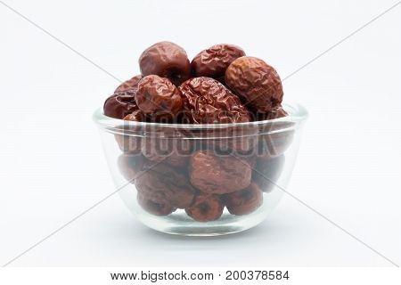 Glass cup of dried red jujube on white background