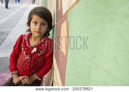 Tehran IRAN - August 16 2017 A little seller girl with a lipstick on hands leaned on colored wall beside street pavement