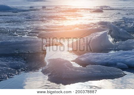 Ice cracked over winter lagoon with sunset tone background Iceland natural landscape background