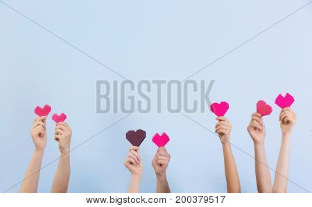 People putting hands in air together with little hearts on light background. Volunteering concept