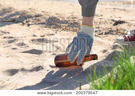 Young person cleaning beach area. Volunteering concept