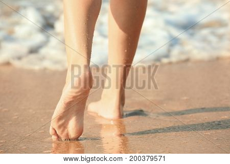 Legs of beautiful young woman at sea resort