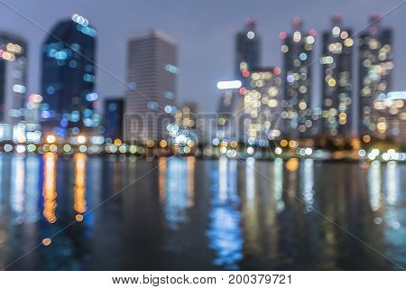 Blurred bokeh city office building light night view water front abstract background