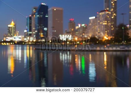 Night light blurred bokeh city office building with water reflection abstract background