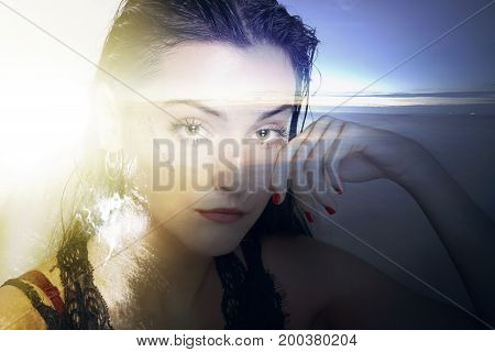 Portrait of a woman looking to the camera and a sunset on a beach. Double exposure.