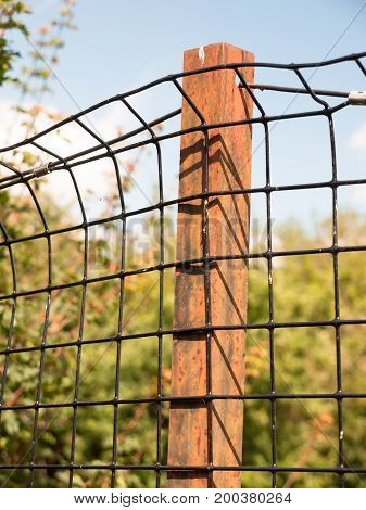 Rusted Metal Iron Bar Holding A Wire Mesh On Protected Field
