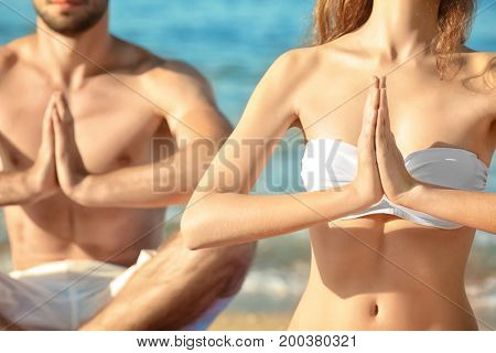 Young couple practicing yoga on sea beach