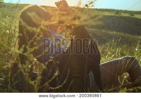 Young girl lies on a hill with a dog in summer sunshine. Sun flare.