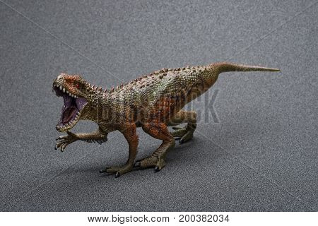 a Carcharodontosaurus toy on a dark background