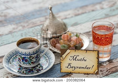 Happy eid text in turkish on greeting card with turkish coffee delights on vintage table poster