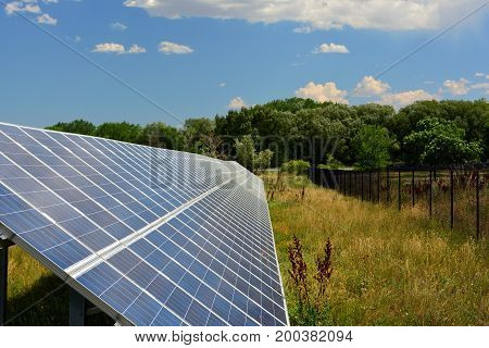 Row of Blue Solar Panels on a Sunny Day with White Puffy Clouds