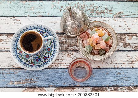 Turkish coffee in traditional cup with glass of water and turkish delights on vintage table top view