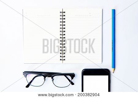 Top view of business working equipment concept with notepadmodern glassespencil and smartphone on white tableflatlay design.