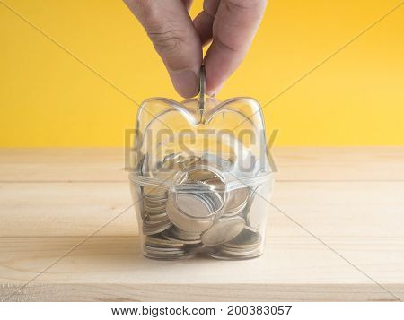 transparent see through piggy bank filled with coins on wood background.Saving investment colorful concept.Hand putting coin into pink piggy bank.