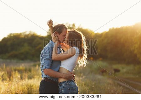 Couple in love. Tenderness and embrace. The guy and the girl are kissing. Sunset sun over the forest.
