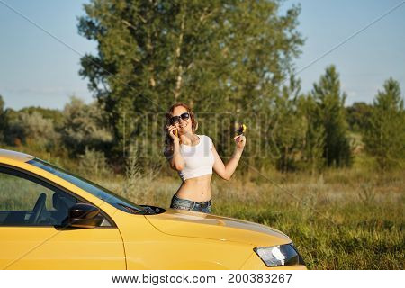 Young attractive girl talking on cell phone. She holds the keys of the car's ignition. Stopover. Call the tow truck.