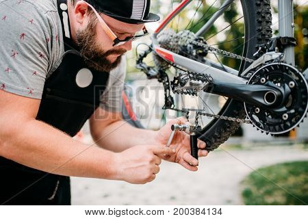 Bicycle mechanic in apron adjusts bike chain