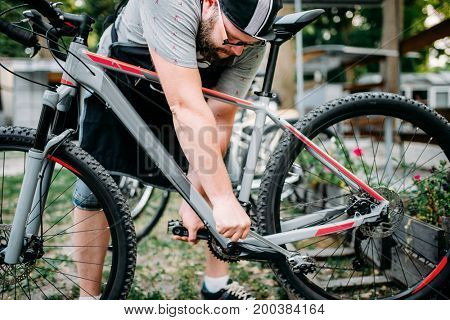 Bicycle mechanic hands adjusts cycling pedals