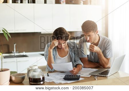 Female And Male Sitting Together Against Kitchen Interior, Having Attentive Look Into Documents, Bei