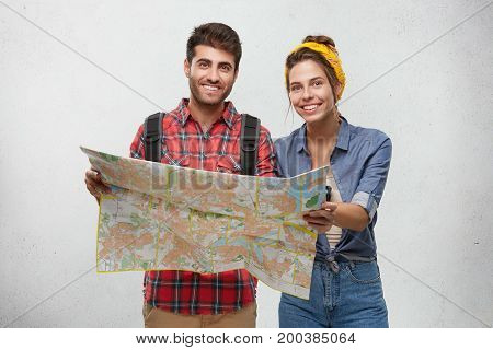 Joyful Young Couple Hikers Studying Paper Map Before Road Trip Around Europe, Anticipating Adventure