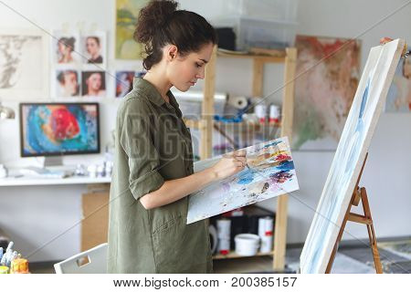 Student Girl Of Faculty Of Arts Wearing Military Green T-shirt Standing In Front Of Easel, Mixing Co