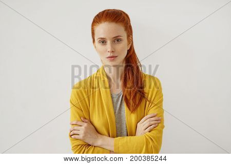 Young Caucasian woman with red hair tied in pony tail having appealing appearance with freckles looking with serious expression while keeping her hands crossed isolated over white background poster