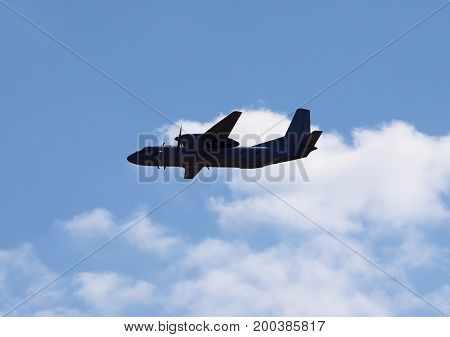 Two-engine military transport aircraft in flight on the background of clouds