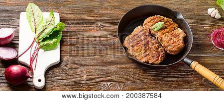 Roasted Steaks In  Pan On A Dark Wooden Table.