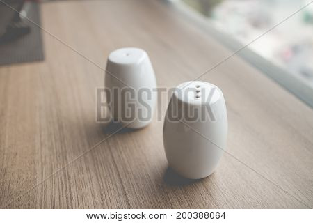 the bottle of salt and pepper on dining table