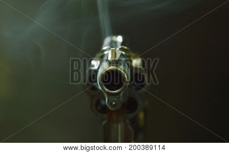 revolver gun muzzle with smoke floating in the air after shoot on black background