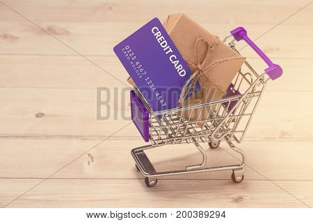 Credit Card And Shopping Cart With Gift Box Wrapped With Paper Kraft On Table.