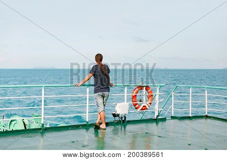 young man traveller standing on the boat and looking at water