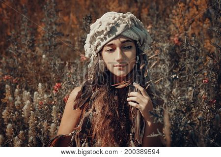 beautiful young woman with turban on a field at sunset