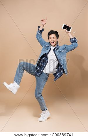 Lifestyle People Concept. Young Pretty Asian Man Jumping Cheerful While Listening To Music.