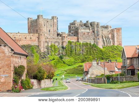 BAMBURGH, UNITED KINGDOM - JUNE 12, 2012: A view of the picturesque village of Bamburgh, in Northumberland in England, with Bamburgh Castle in the background.