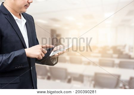 businessman using the mobile phone blurred of conference hall or seminar room background.