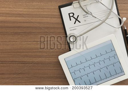 Cardiograph Ekg Electrocardiogram Heart Showing In Tablet Computer And Rx Medical Documents On Desk