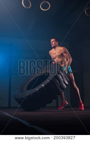 Full length picture of muscular fitness model exercising with tire in gym. Weightlifting or functional workout. Sports and fitness concept.