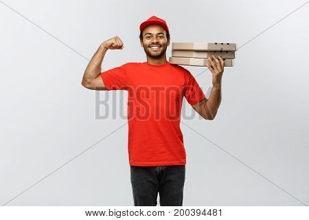 Delivery Concept - Portrait of Strong African American delivery man showing his muscle with pizza box packages. Isolated on Grey studio Background. Copy Space.
