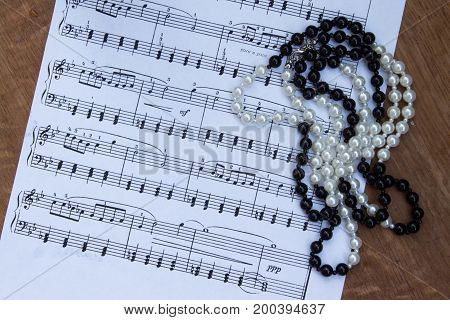 Necklace  On Background  Music Notes. Trip To The Theater. Top View.