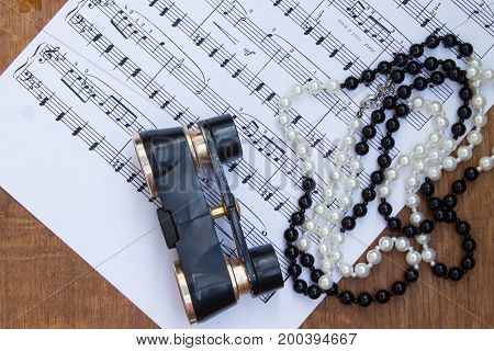 Binoculars And Necklace On Background Of Music Notes.