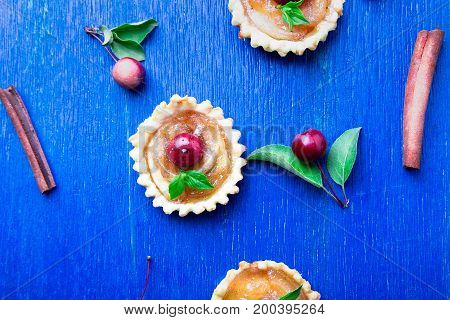 Apple Caramel Little Tarts On Blue Rustic Background. French Tatin With Paradise Apple. Top View. Fr