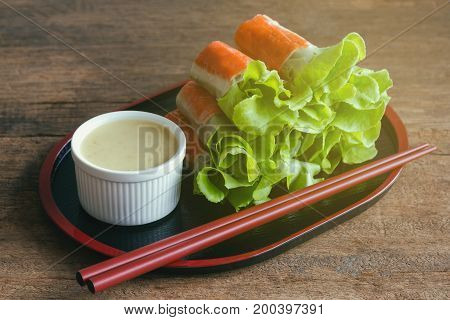 Fresh spring rolls with fresh vegetable and crab stick served with wasabi mixed salad cream dipping sauce.Rolls salad or fresh spring roll in Japanese style healthy tasty food for appetizer or meal.Delicious fusion food: fresh spring rolls.