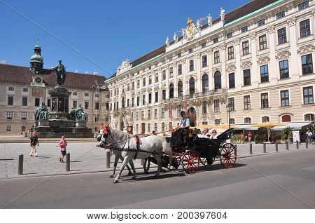 Vienna, Austria - August 2012: Hofburg in Vienna, Austria in August 2012, with people walking through or riding a horse carriage