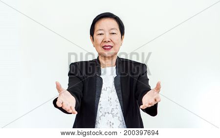 Asian senior woman wearing suit with happpy face and hand gesture