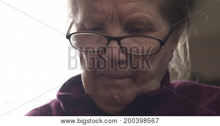 old woman wearing glasses doing something, wide photo
