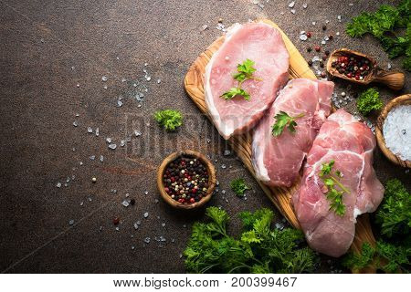 Fresh meat. Raw pork steak on a cutting board with herbs and spices on dark stone table. Top view copy space.