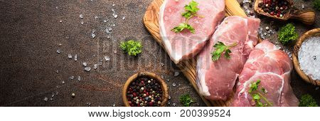 Fresh meat. Raw pork steak on a cutting board with herbs and spices on dark stone table. Long banner format.
