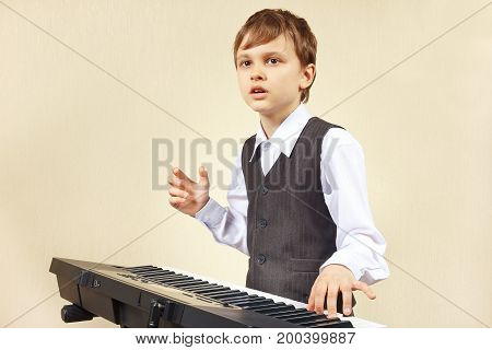 Little beginner pianist play the keys of the electronic organ