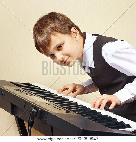 Young beginner pianist in a suit playing the electronic piano